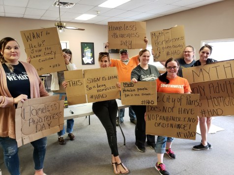 Lamar County Homeless Coalition members hold up signs they created to educate community members on Homelessness Awareness Day.
