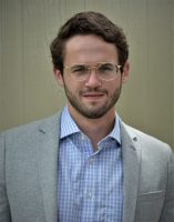 A young Caucasian man with short brown hair, a neatly trimmed beard, and large gold framed glasses stands in front of a wood panel background wearing a blue plaid button-down shirt and a tweed blazer.