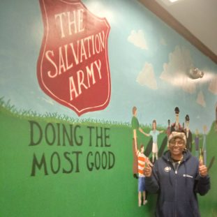 Brenda standing in front of a mural at the Salvation Army