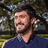 Greg Casar smiling in front of a blurred background of lush green grass and trees.