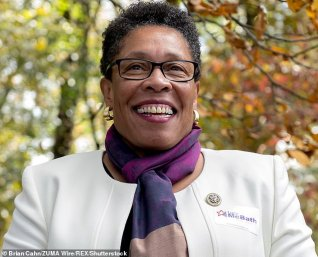 Secretary Fudge smiling in a white top and tightly wrapped mutli-color purple scarf outside in the fall with leavings changing in the background.