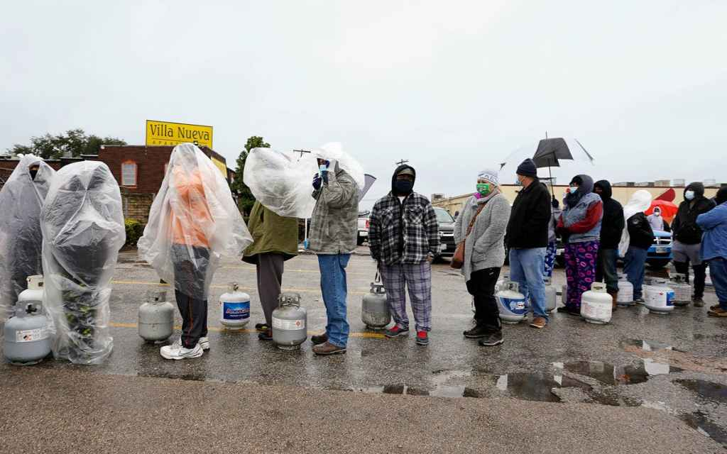 People standing in raincoats and winter gear outside in a parking lot waiting to refill propane tanks.