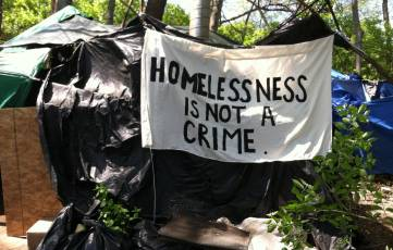 Homelessness is not a crime painted on a canvas sheet hanged over an outdoor home of an unhoused neighbor.