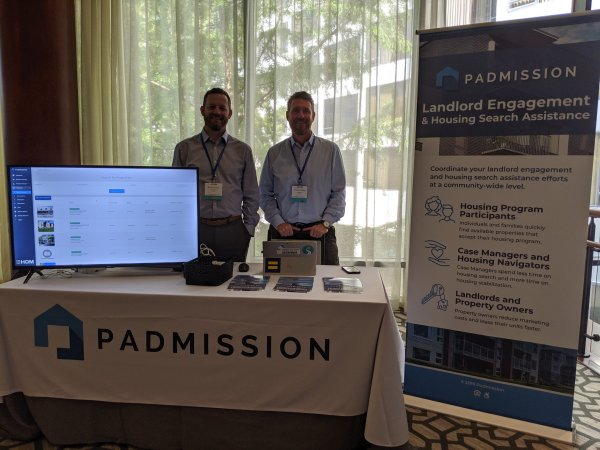 Two men standing behind an exhibit table for PadMission.