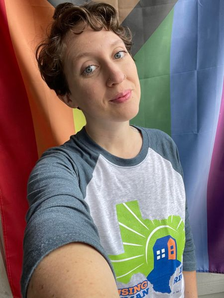 Kyra smiling with their head slightly tilted in their homelessness awareness tee. Draped behind them is a rainbow flag.