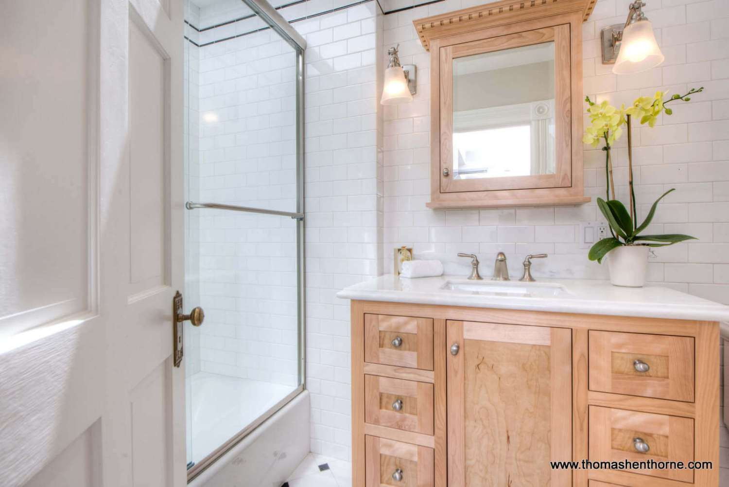 photo of door opening into bathroom with white tile