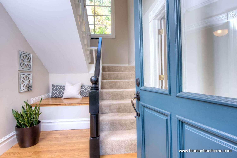 front door opening onto stairway with window in background