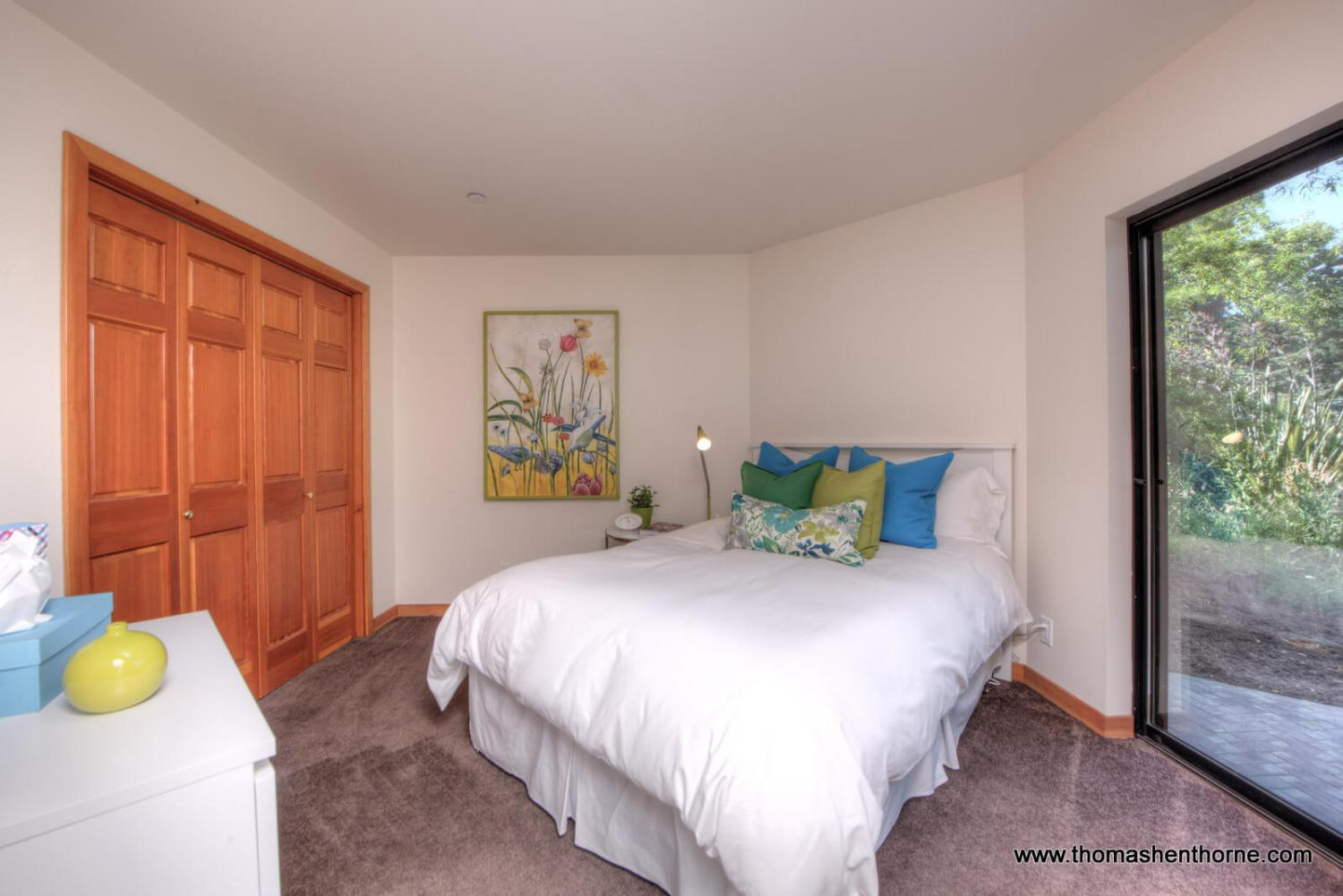 Guest room with white comforter on bed and slider to right