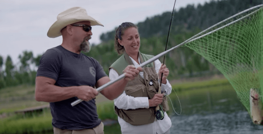 Photo of Liz O'Neill and John Nelson catching a fish from trout pond in Houseguest Episode Three
