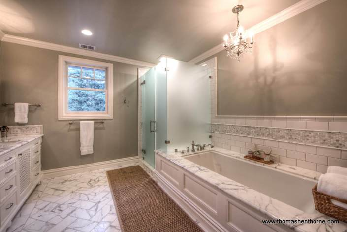 master bathroom with marble floor and bathtub