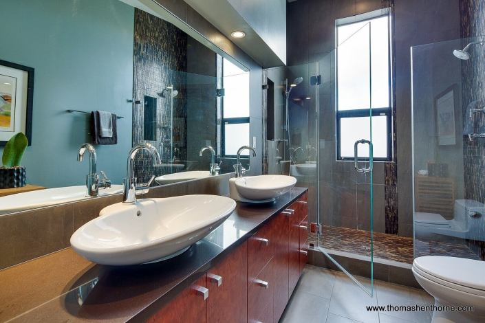 Master bathroom with dual vessel sinks and glass enclosed shower with view