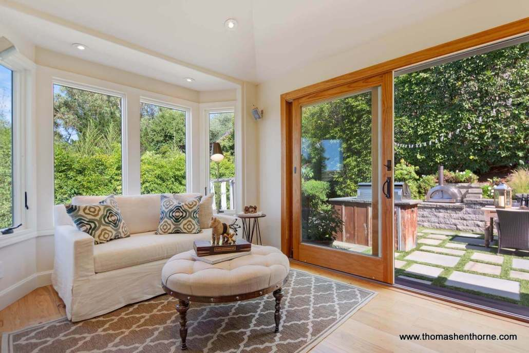 Room with love seat and glass sliding doors to backyard pizza oven