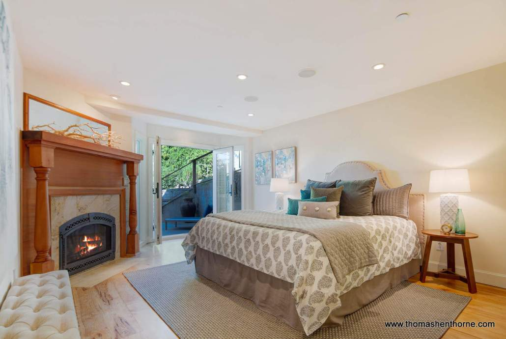 Bedroom with fireplace and open French doors to outside