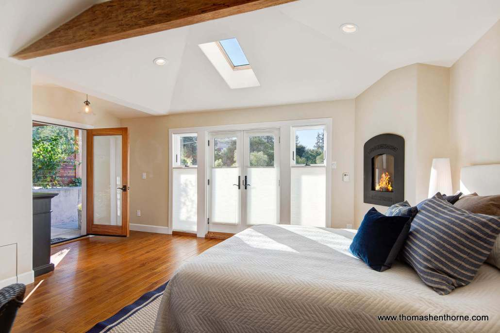 Bed with beamed ceiling wood floors and fireplace
