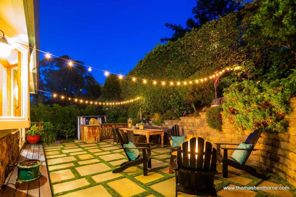 Patio with string lights and Adirondack chairs at dusk