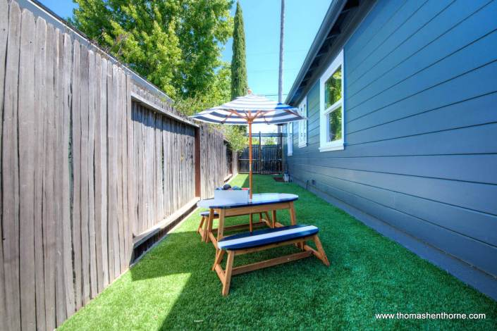 Side yard play area with kidstable and umbrella