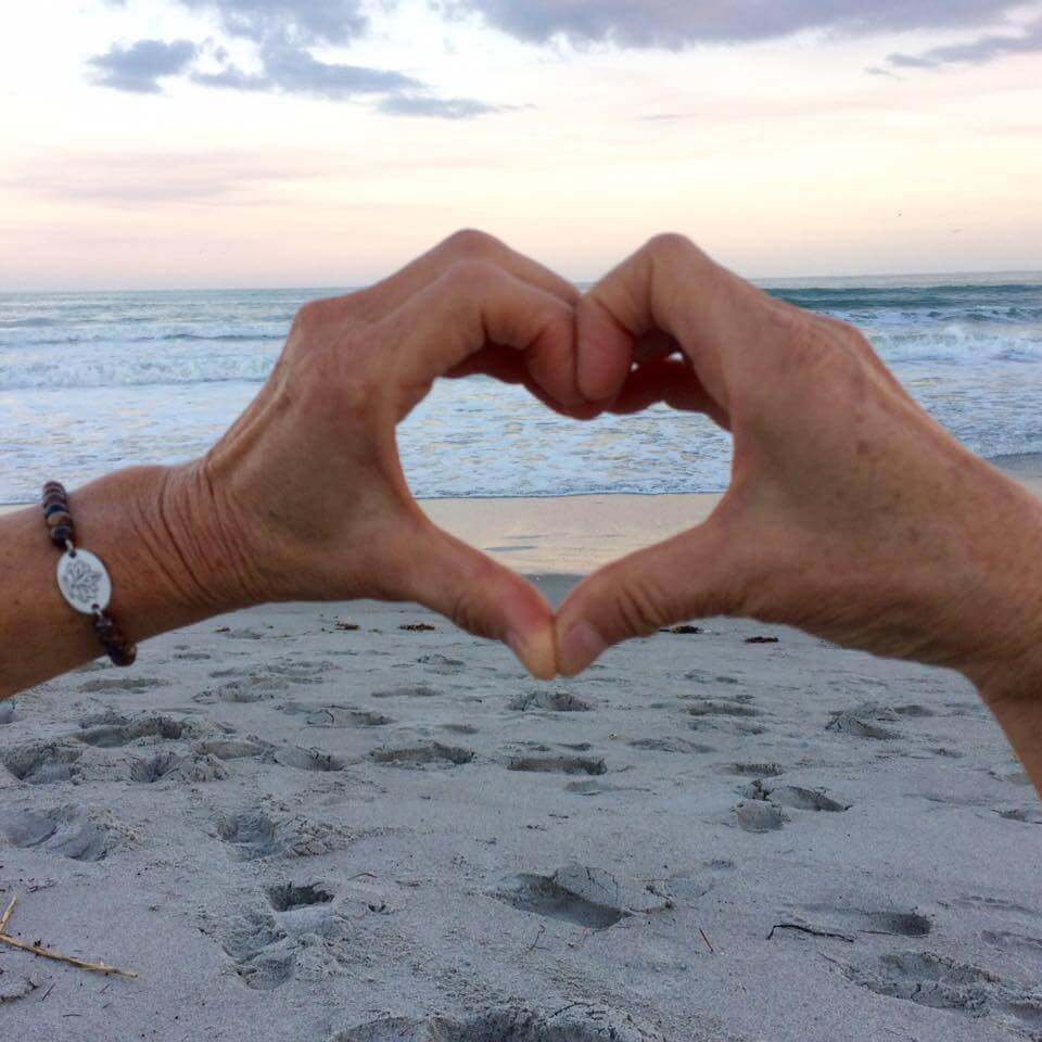 Sukha Yoga hands forming a heart on a beach