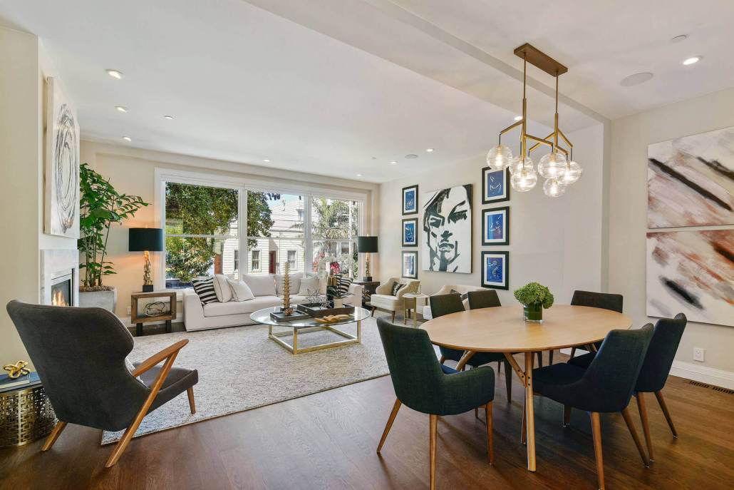 Open living dining area with fireplace and windows