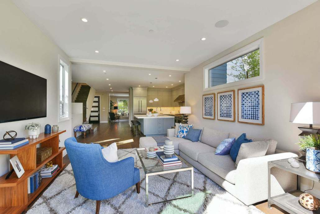 Modern luxury family room with glass coffee table and blue chair