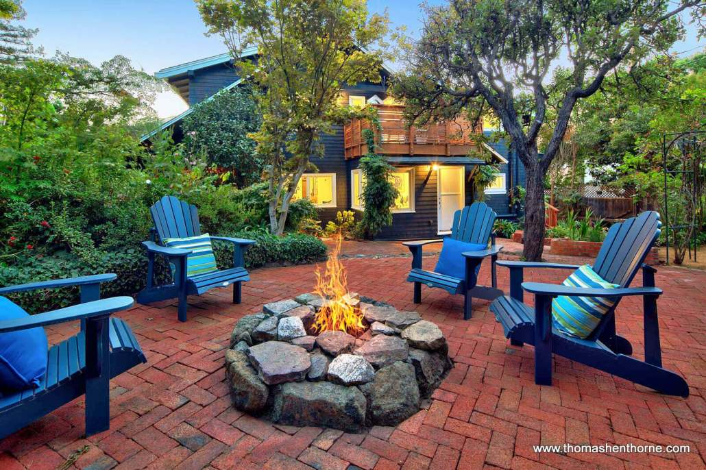 lit fire pit with four Adirondack chairs