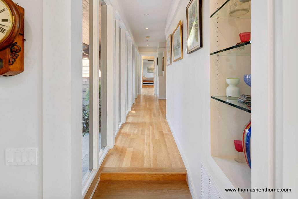 Hallway with wood floors and art on walls
