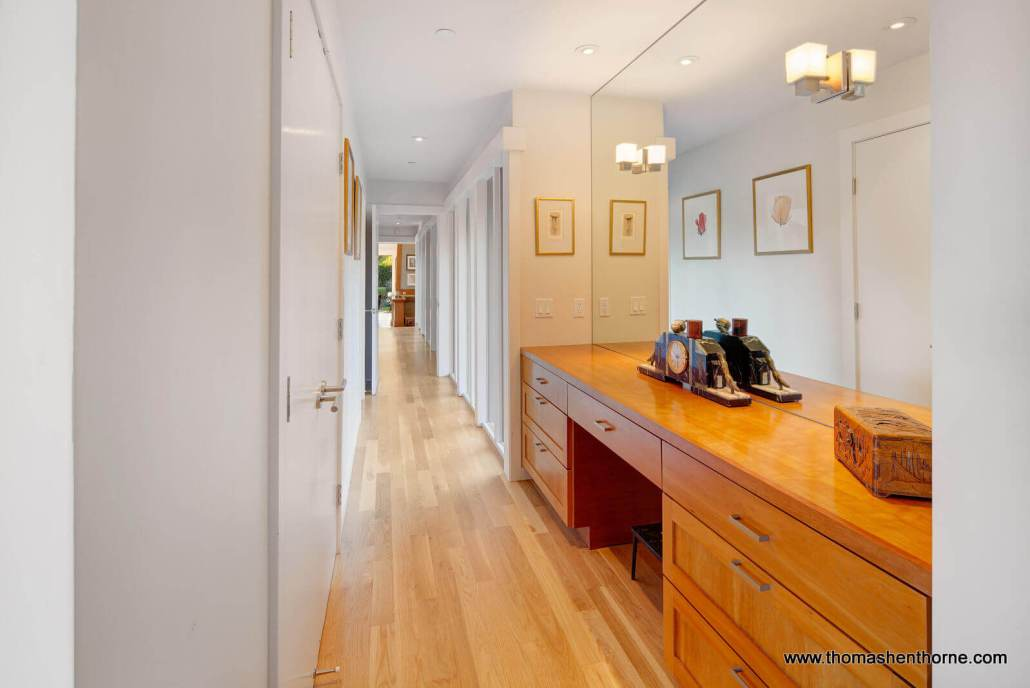 Hallway with wood floors and built-in cabinetry