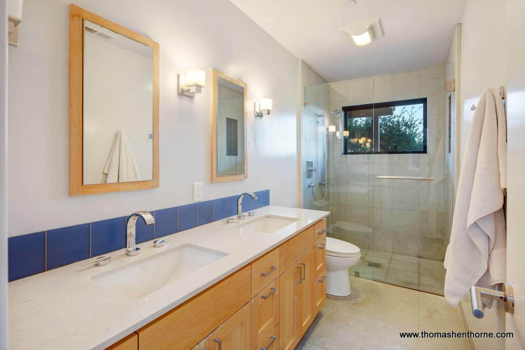 Dual sink bathroom with shower stall made of glass
