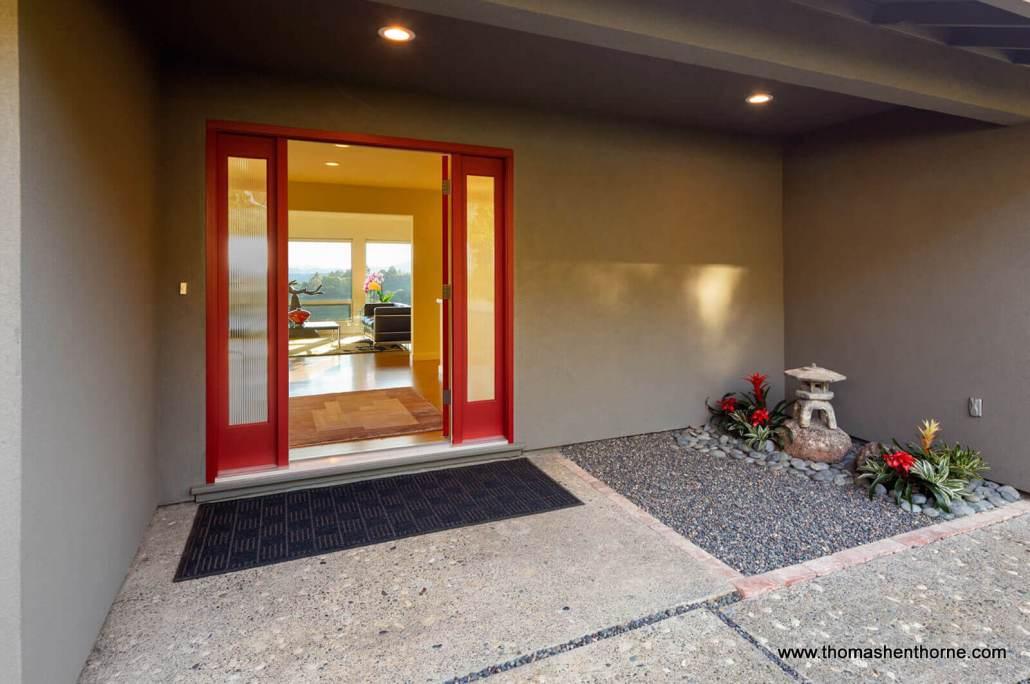Red front door with view of room in distance