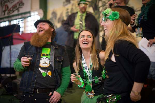 People laughing drinking beer and dressed for St. Patrick's Day