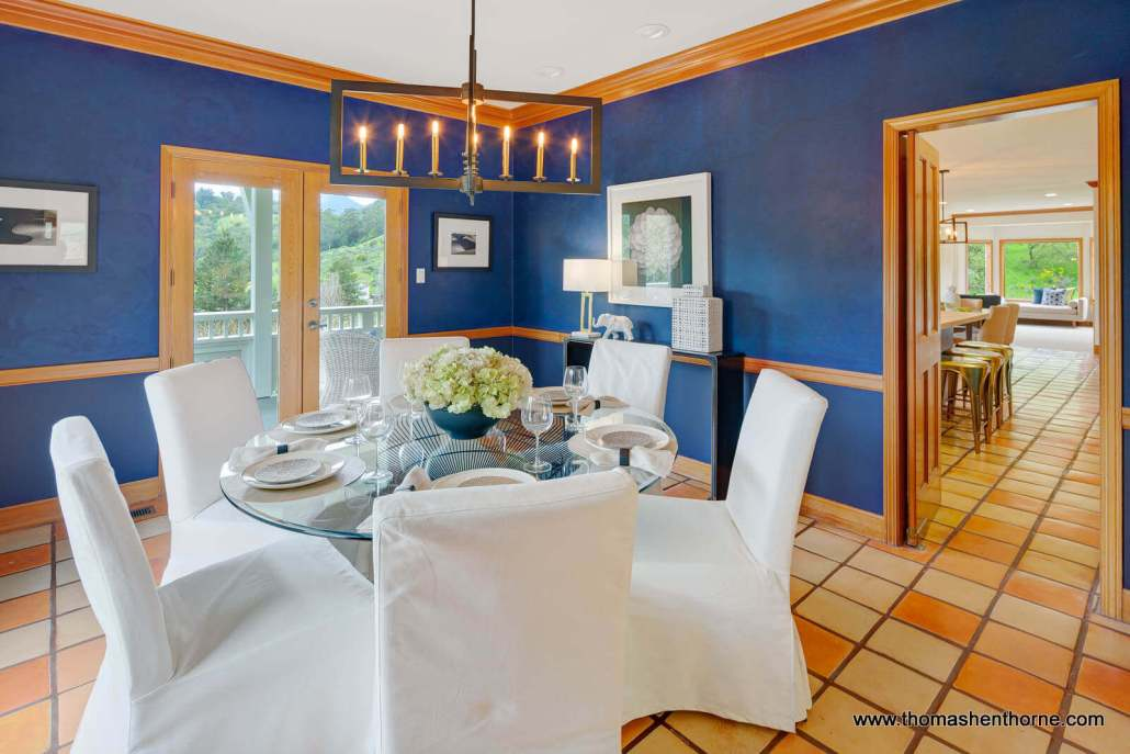 Dining room with round glass coffee table and blue walls