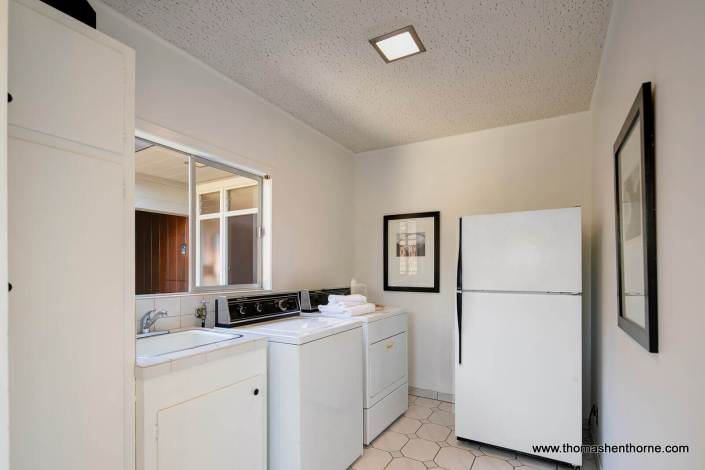 Laundry room with refrigerator