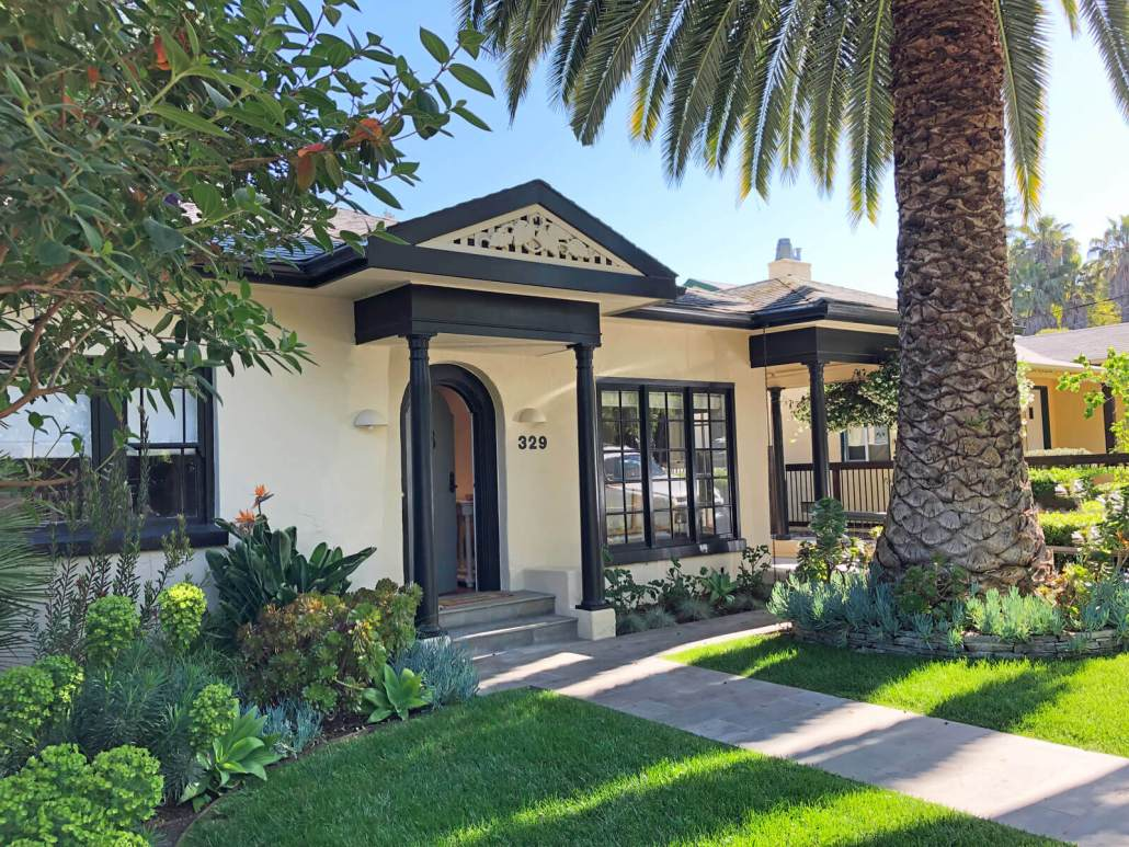 Front exterior of bungalow in San Anselmo, California with green lawn and large canary island palm