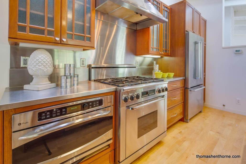 Kitchen with stainless appliances and hood