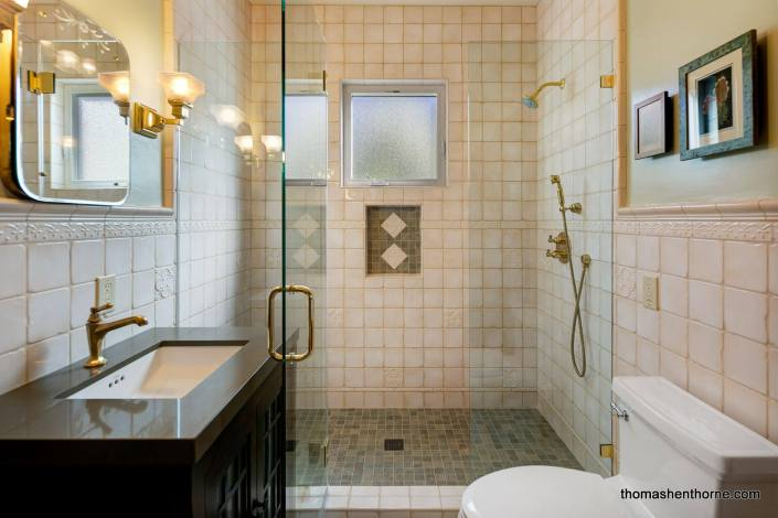 Bathroom with custom tilework and brass fixtures