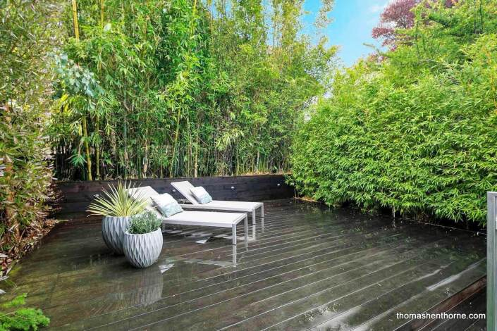 Two chaise lounges on deck surrounded by bamboo