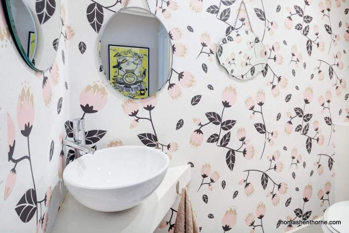 Half bathroom with floral wallpaper