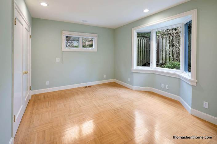 Room with green walls and white trim and parquet floors