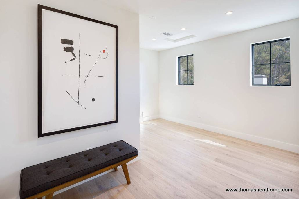 Large empty room with wood floors and bench and art on wall