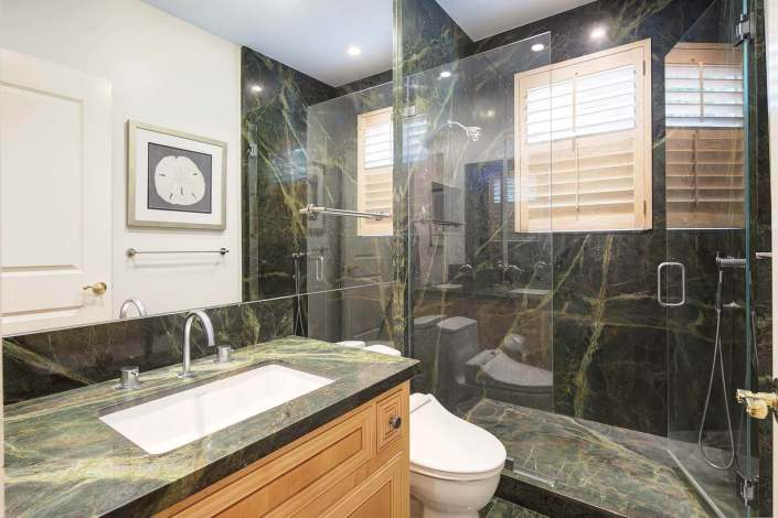 bathroom with stone countertops and glass shower