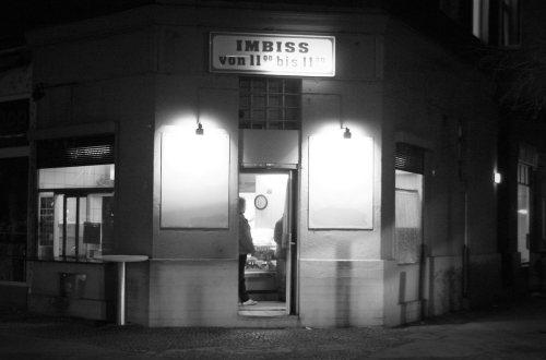 """Nachts in einer Stadt: eine Eckkneipe, auf der """"Imbiss von 11 bis 11"""" steht. Ein Mann steht im Türbereich."""