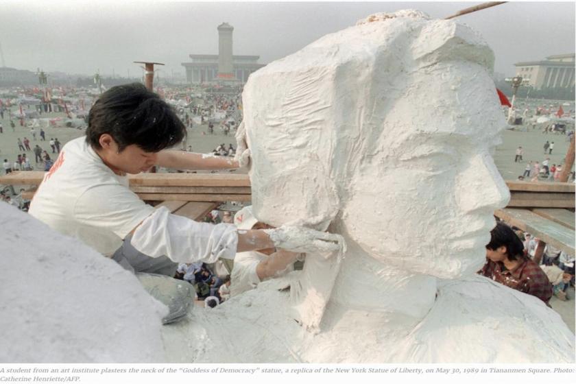 """Ein chinesischer Kunststudent arbeitet an der """"Göttin der Demokratie"""" in Peking im Mai 1989 © Catherine Henriette (AFP)"""
