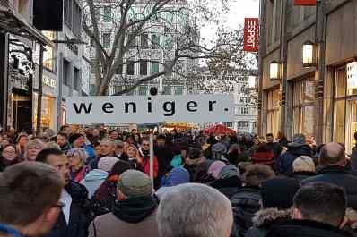 """Blick in die Kölner Hohe Straße voll mit Menschen und einem Schild, auf dem """"weniger."""" steht. © Tom Rübenach"""
