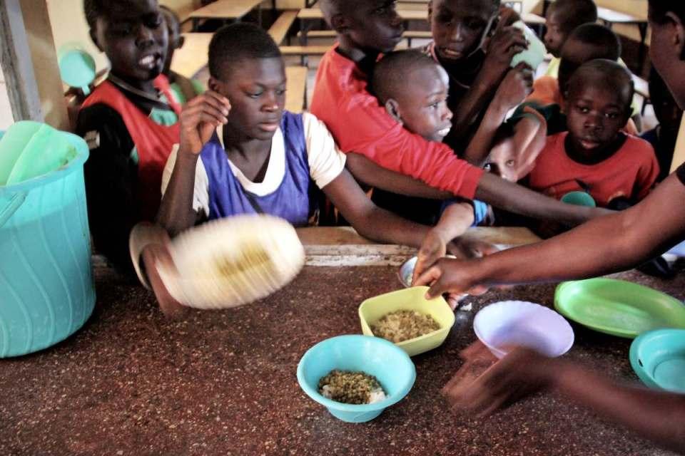 Kinder im Ayiera-Center im Slum Korogocho erhalten Mittagessen. Sie haben Plastikschüsseln mit Reis und ein paar Erbsen. | Foto © Tom Rübenach