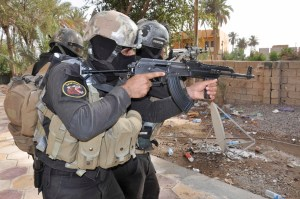 Armed Iraqi security forces personnel take their positions during a patrol in the city of Ramadi
