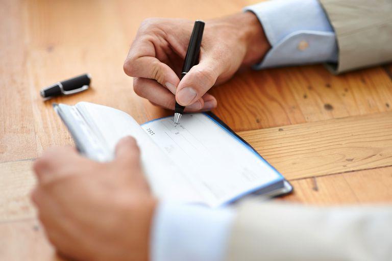 Varón firmando un cheque