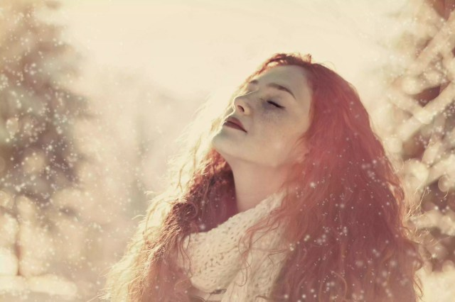 Beautiful young woman raising her head to snow