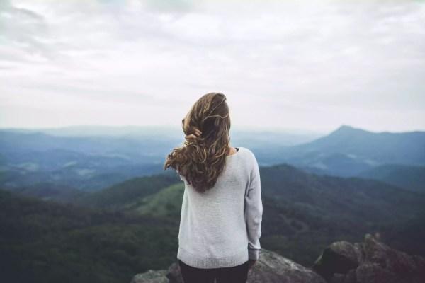Mulher olha para fora em uma cena de montanha bonita