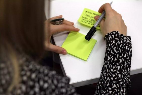 Vista alta ângulo, de, mulher, escrita, adesivo, nota, tabela