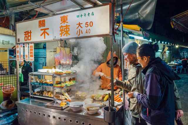 Caucasian Male and Asian Female in Outdoor Taiwanese Night Market Standing in Front of Food Vendor