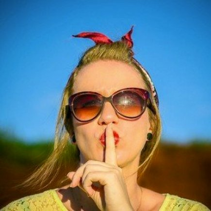 Woman Wearing Sunglasses with Finger on Mouth Saying Shhh